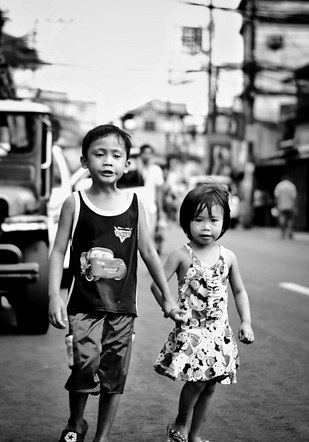 Brother and sister, strolling down the street.